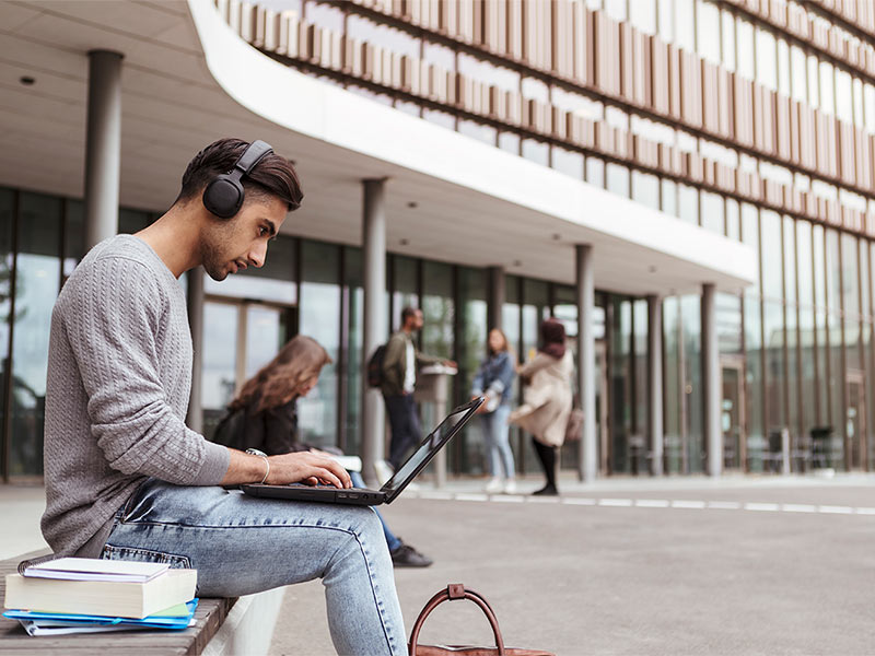 A student wearing headphones and working on laptop